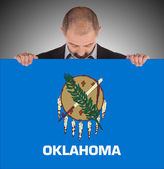Smiling businessman holding a big card, flag of Oklahoma — Stok fotoğraf
