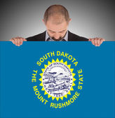 Smiling businessman holding a big card, flag of South Dakota — Photo