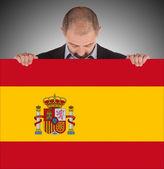 Empresario sonriente sosteniendo una tarjeta grande, bandera de españa — Foto de Stock