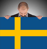 Smiling businessman holding a big card, flag of Sweden — Stock Photo