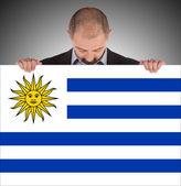 Usměvavý obchodník drží velkou kartu, vlajka uruguaye — Stock fotografie