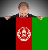 Businessman holding a big card, flag of Afghanistan — Stock Photo