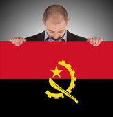Businessman holding a big card, flag of Angola — Photo