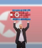 Affärsman som innehar en stor bit av en vägg — Stockfoto