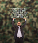 Businessman holding a large piece of a brick wall — Stock Photo