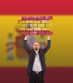 Businessman holding a large piece of a brick wall — Stockfoto