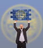 Businessman holding a large piece of a brick wall — 图库照片