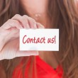 Woman in red showing a business card — Stock Photo