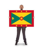 Smiling businessman holding a big card or flag — Stockfoto