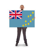 Smiling businessman holding a big card or flag — Stock Photo