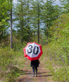 Woman in the forrest with a traffic sign umbrella — Stock Photo