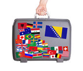 Used plastic suitcase with stickers — Stock Photo