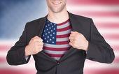 Zakenman opening pak te onthullen shirt met vlag — Stockfoto