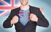Businessman opening suit to reveal shirt with flag — Stock Photo