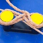 Twisted orange rope round a yellow bollard — Stock Photo #50387053