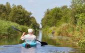 Man paddling in a blue kayak — Stock Photo