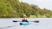 Woman on a small river in rural landscape — Stock Photo