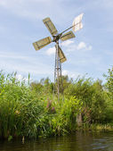 Small and rusted old metal windmill at the waterside — Stock Photo