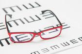 Reading eyeglasses and eye chart — Stock Photo