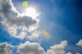 Blue sky with white fluffy clouds and sun — Stock Photo