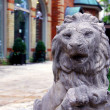 Stone statue of lion guarding houses - Stock Photo