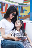 Little Asian girl and mom using tablet PC in shopping mall. — Zdjęcie stockowe