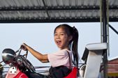 Little Asian girl driving toy car in amusement park. — Stock Photo