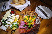 Meat and Cheese with Vegetables on a Wooden Plate — Stock Photo