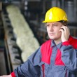 Industrial worker talking on cell phone — Stock Photo