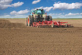 Tractor cultivating field — Stockfoto