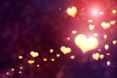Golden shiny hearts on violet background — Stock Photo
