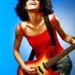 Sensual woman playing on the electric guitar - Stock Photo