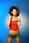 Beautiful woman with afro hair closed her eyes enjoying music with headphones . — Stock Photo