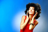 Beautiful smiling woman with afro hair listen to music with headphones — Stock Photo