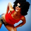 Smiling tanned womwith afro hair posing against blue background — Stock Photo #22264695