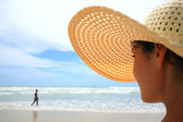 Beautiful woman with big straw hat looking at a man walking on the beach — Stock Photo