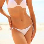 Slim female body in bikini and guys playing fresbee on the beach — Stock Photo