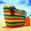 Colorful straw bag, sunglasses, bottle of sun lotion and starfish on paradise tropical beach — Stock Photo