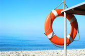Red buoy hanging on rescue tower on the pebble beach. Safety concept — Stock Photo