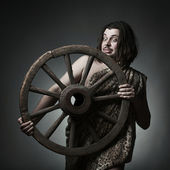 Caveman wearing leopard skin hold old wooden wheel. — Stock Photo
