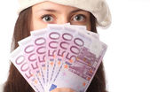 Close-up of woman�s eyes and fan of Euro banknotes — Stock Photo