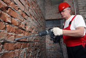 House-builder in uniform working with a plugger — Stok fotoğraf