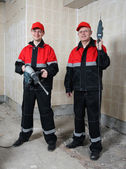 Two smiling house-builders in uniform holding construction tools — Stock Photo