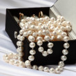 Pearls and rings in black jewelry box — Stock Photo