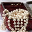 Pearls and rings in red jewelry box — Stock Photo
