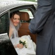 Young charming bride looking out of a car — Stock Photo #14089284