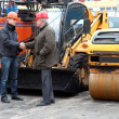Two managers of the works in hard hats shaking hands - 图库照片
