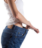 Slim young woman in big jeans — Stock Photo