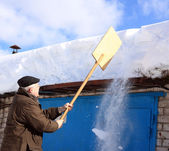 Mann, die schneeräumung von einem dach mit einer schaufel — Stockfoto