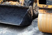 Close-up of frontal loader's scoop and road roller — Stock Photo